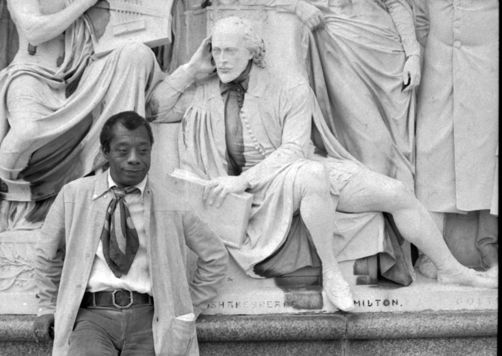 James Baldwin in front of a statue of William Shakespeare.